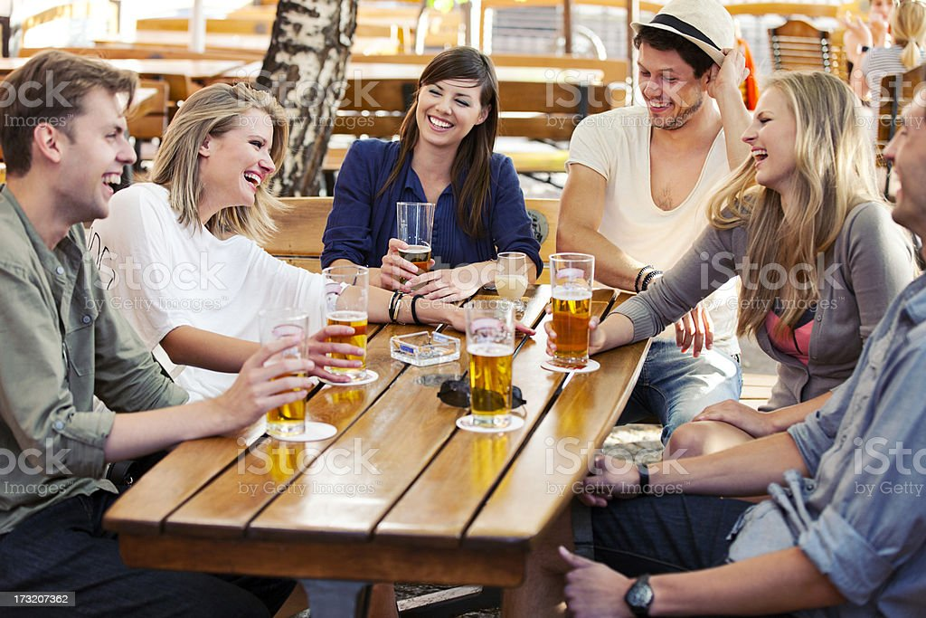 Friends drink and laugh while at a sidewalk cafe stock photo