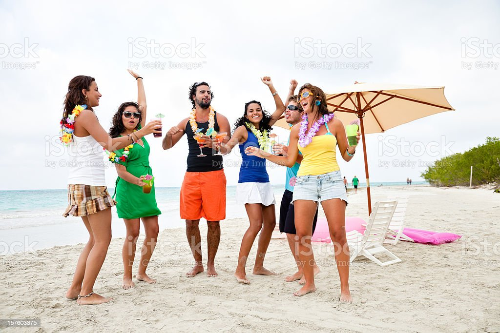 Friends drinking and dancing during beach party stock photo
