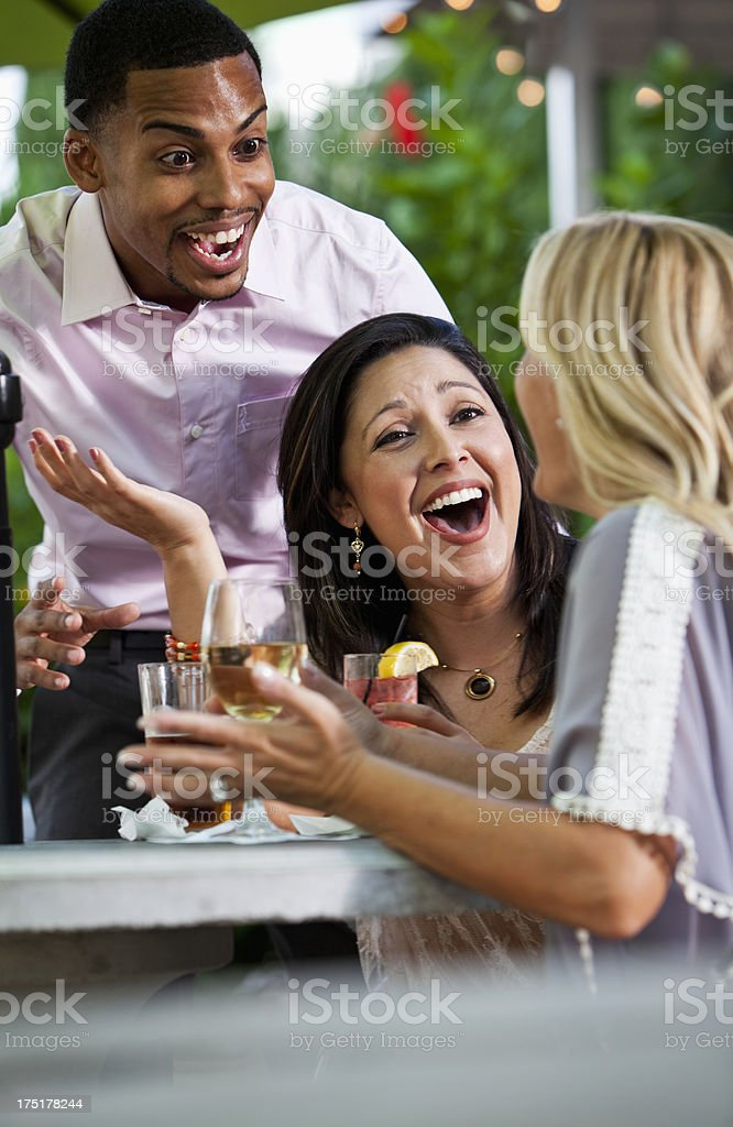 Friends drinking and laughing on patio stock photo