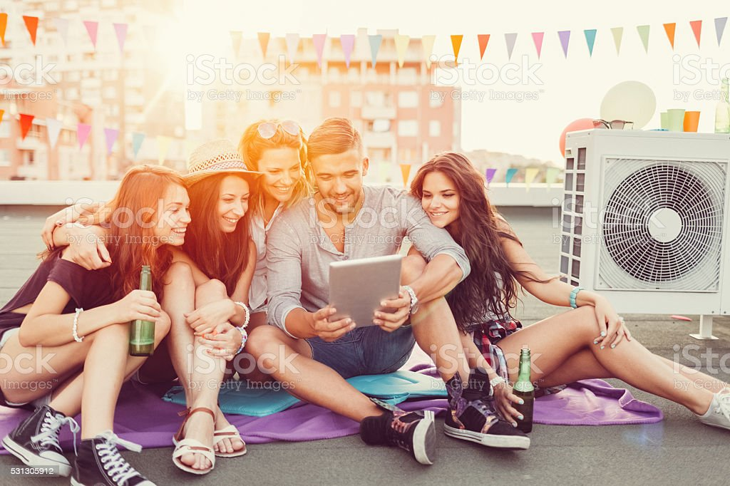 Friends drinking beer and using tablet pc on the rooftop stock photo