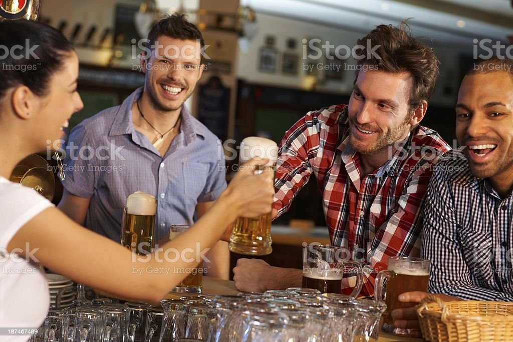 Friends drinking beer at counter in pub stock photo