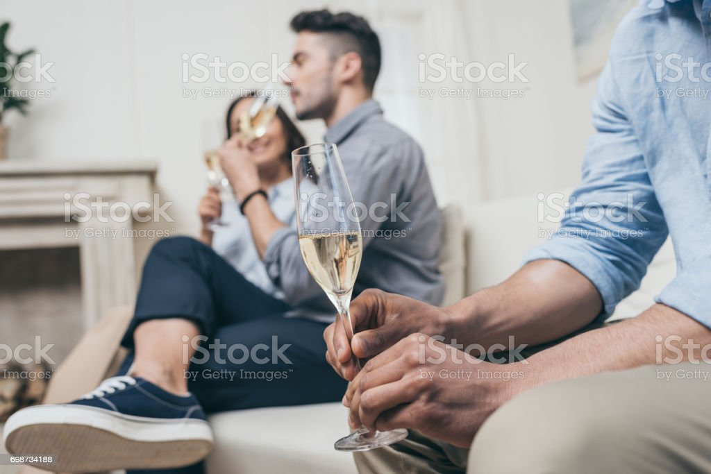 friends drinking champagne from glasses while sitting on sofa at home stock photo
