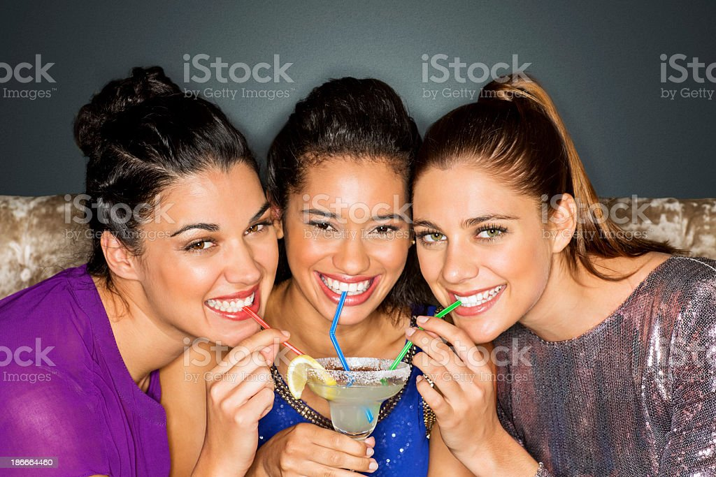 Friends Drinking Cocktail Together Through Straw At Nightclub stock photo