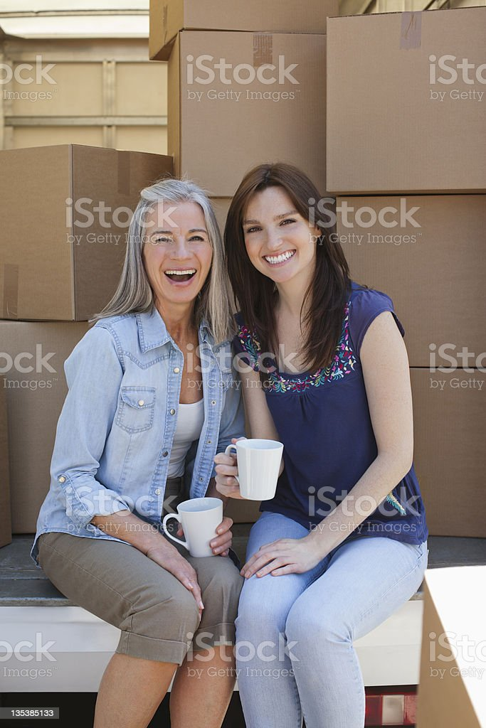 Friends drinking coffee on back of moving van royalty-free stock photo
