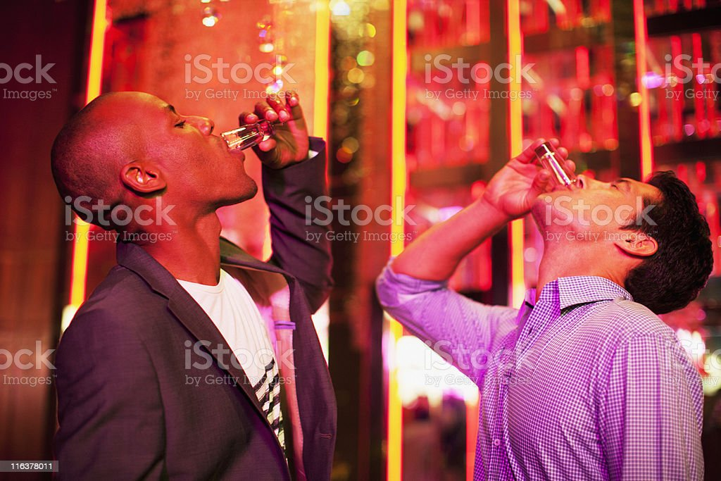 Friends drinking from shot glasses in nightclub stock photo