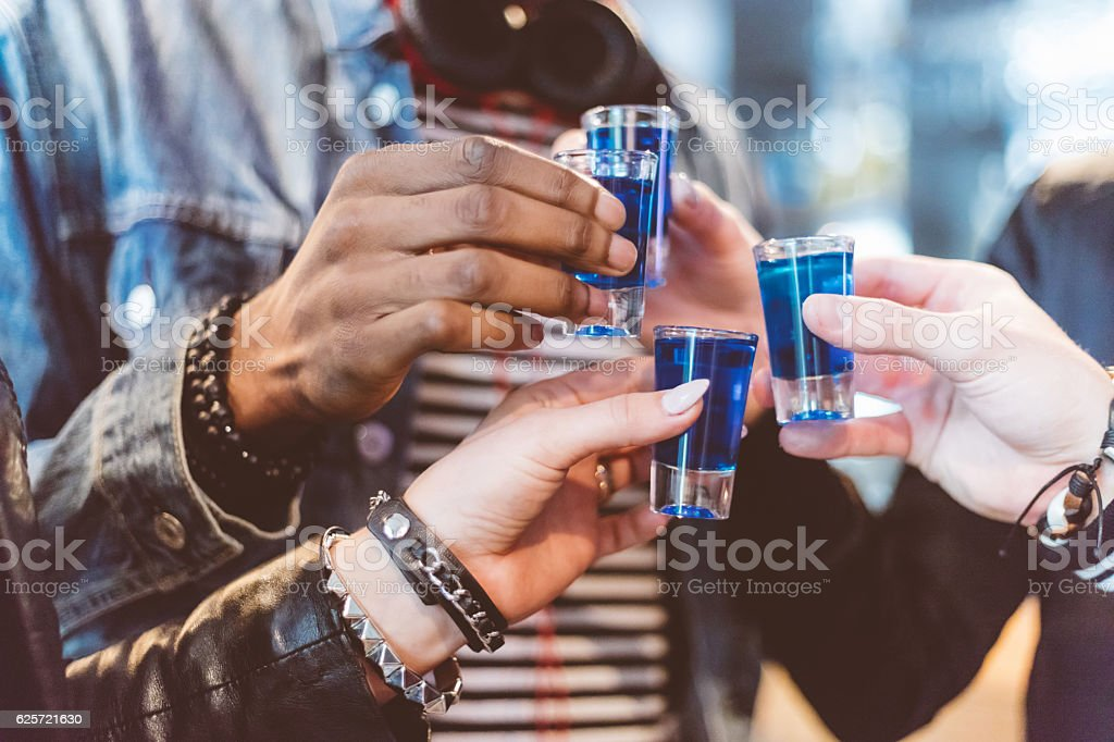 Friends drinking shots, close up of hands stock photo