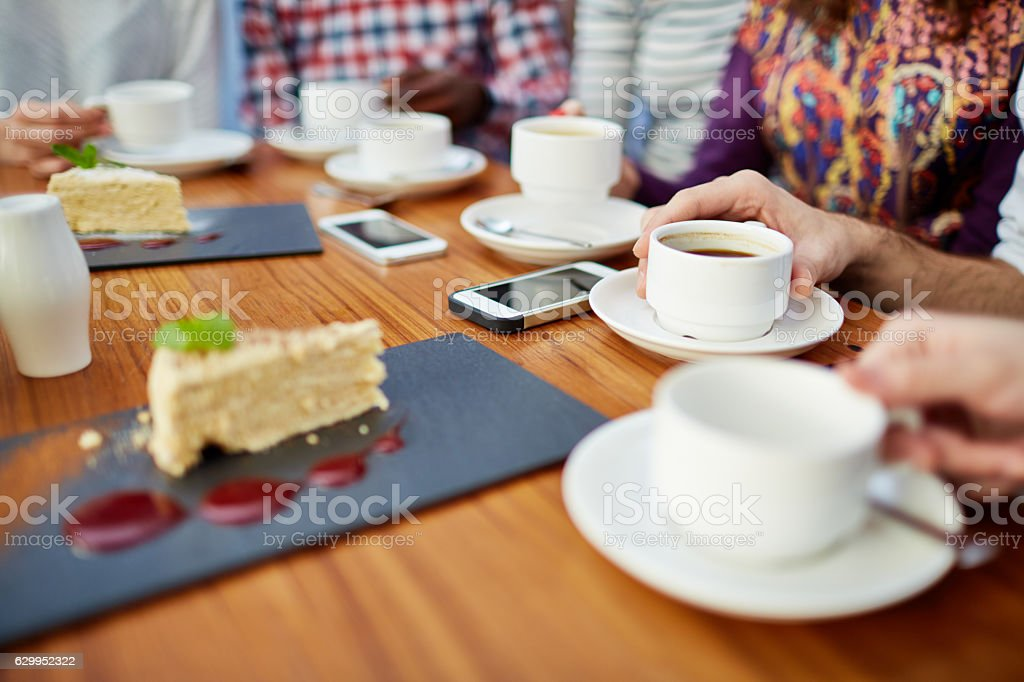 Friends drinking tea and coffee in cafe stock photo