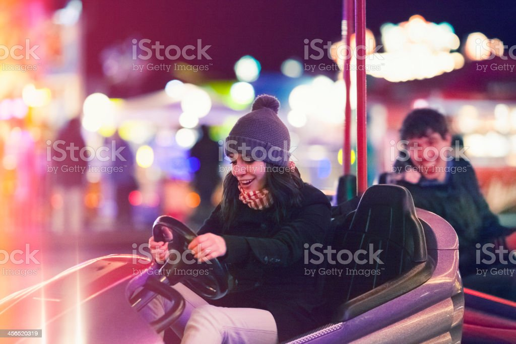 Friends driving bumper cars stock photo
