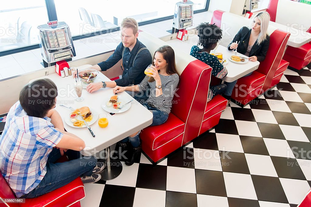 Friends eating at the table in the diner stock photo