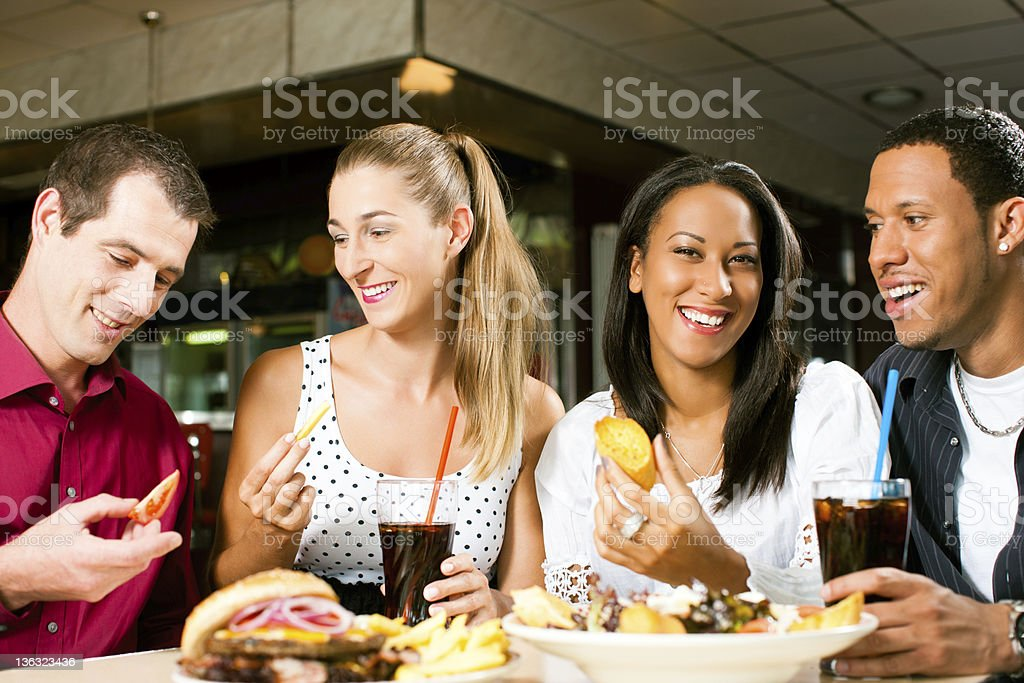 Friends eating hamburger and drinking soda stock photo