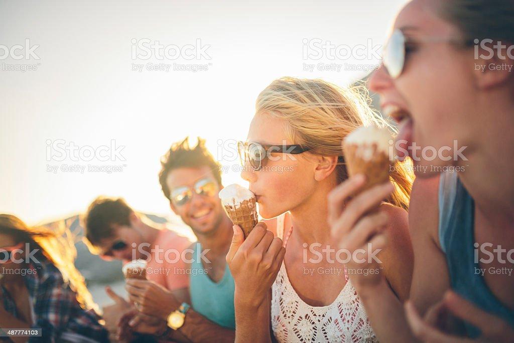 Friends eating icecream on beach stock photo