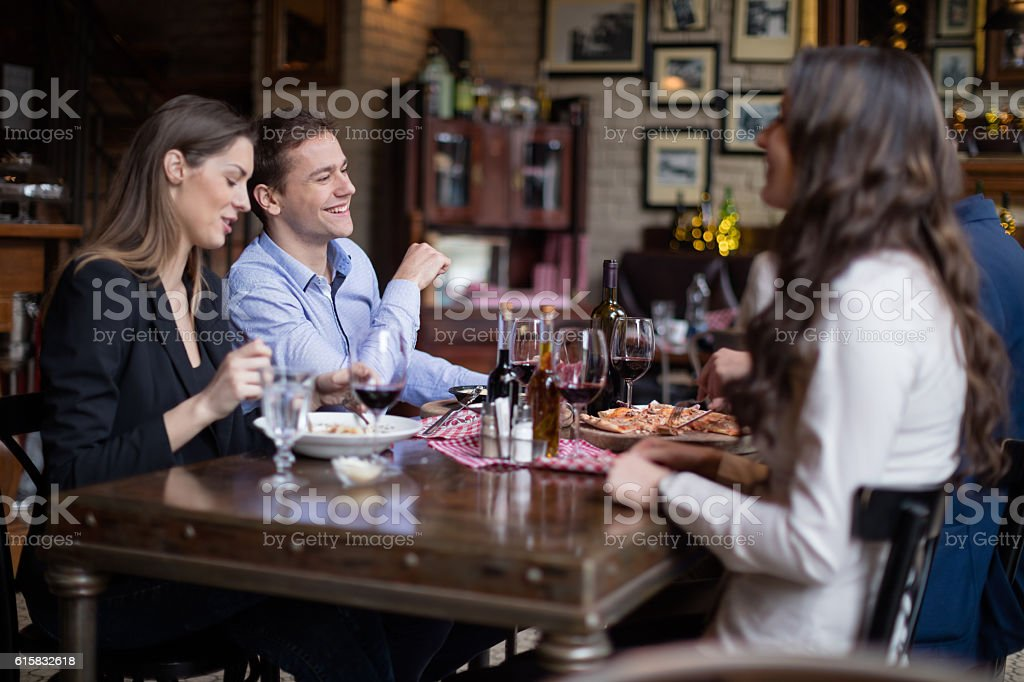 Friends eating italian food in restaurant stock photo