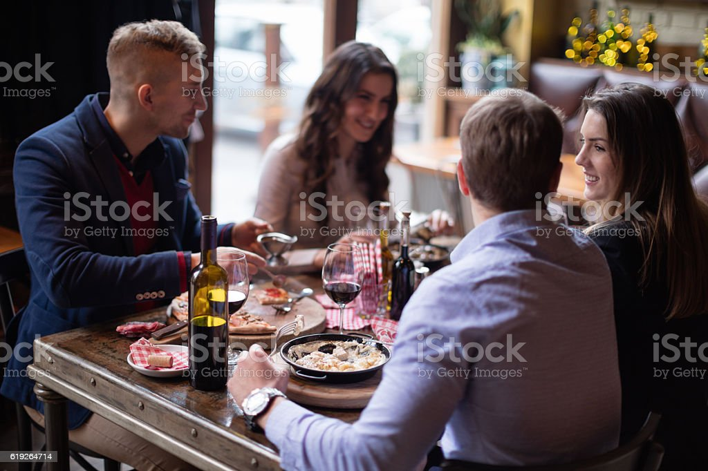 Friends eating italian food in restaurant stock photo