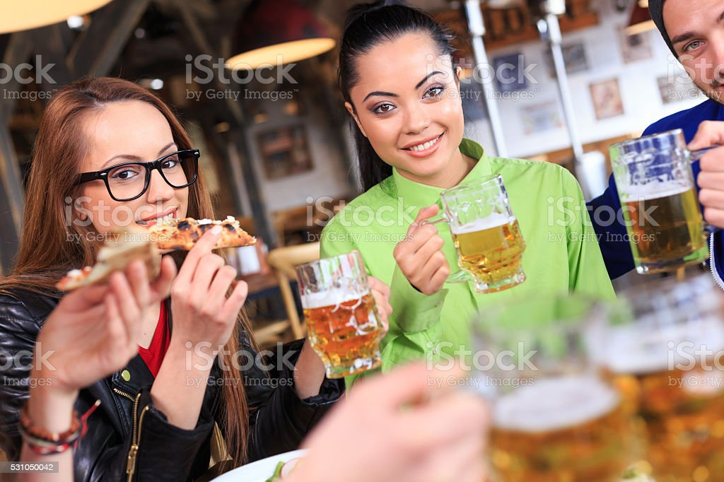 Friends eating pizza and drinking beer at restaurant stock photo