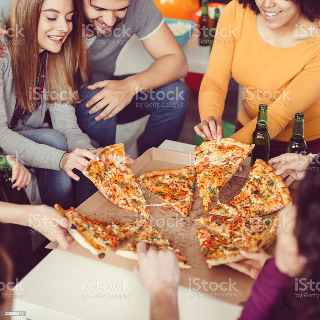 Friends eating pizza at home stock photo