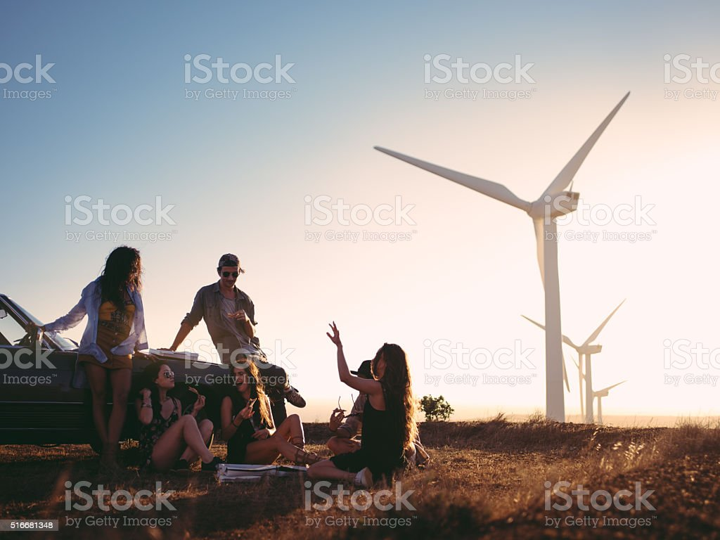 Friends eating pizza at sunset on an american road trip stock photo