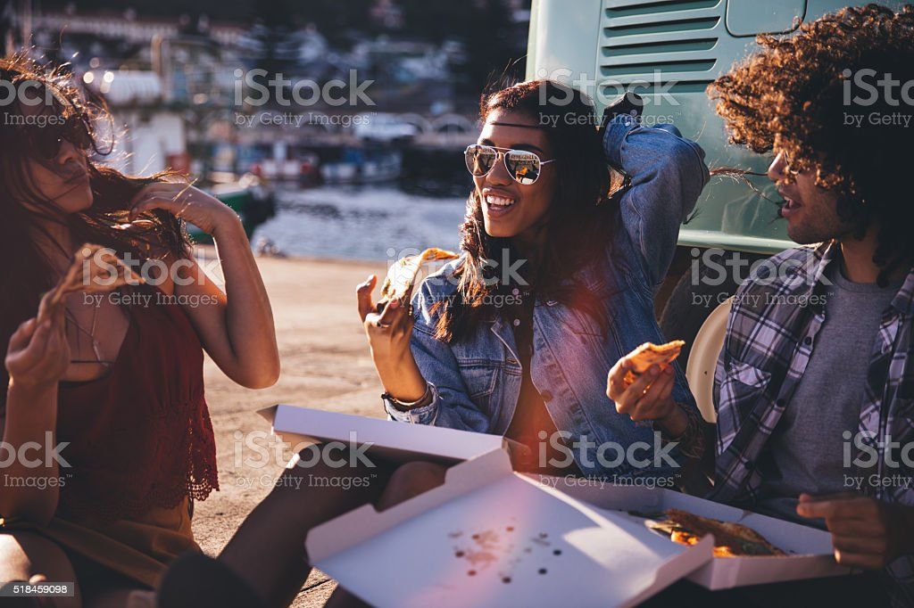 Friends eating pizza at the harbor close to vintage van stock photo