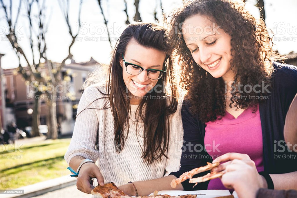 Friends eating Pizza at the park stock photo