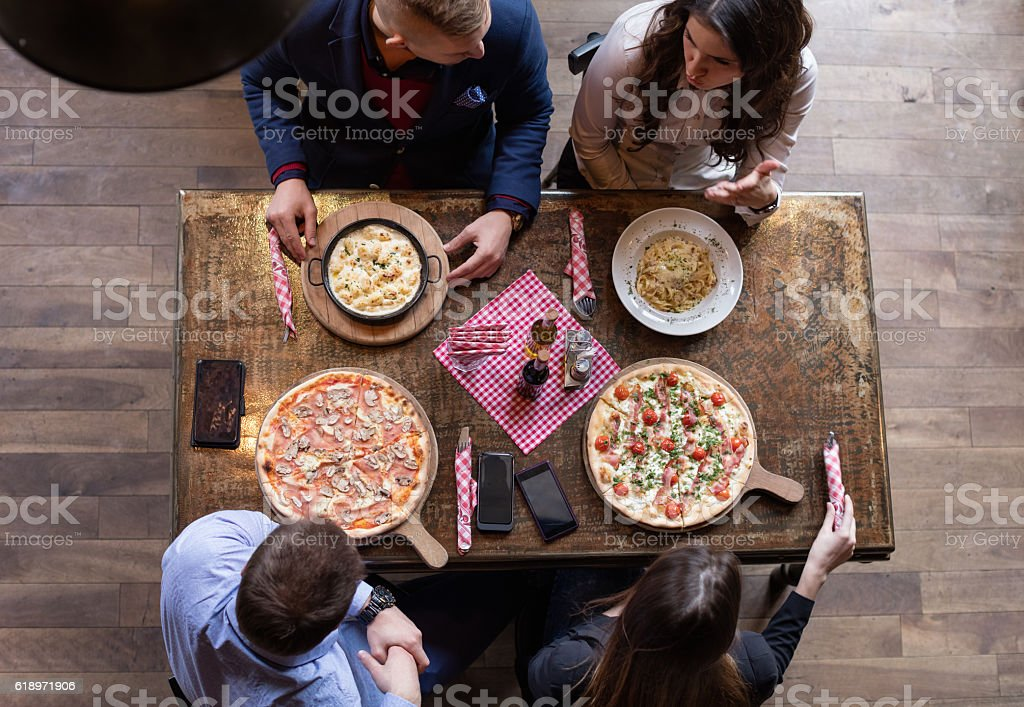 Friends eating pizza, elevated view stock photo