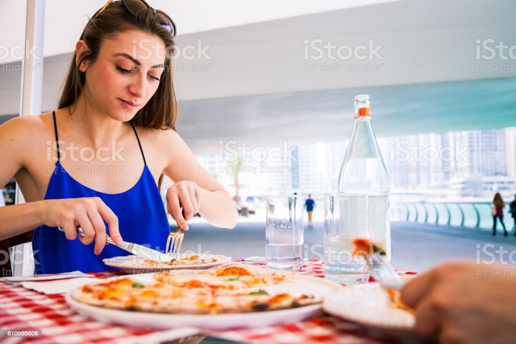 Friends eating Pizza in a sidewalk restaurant stock photo