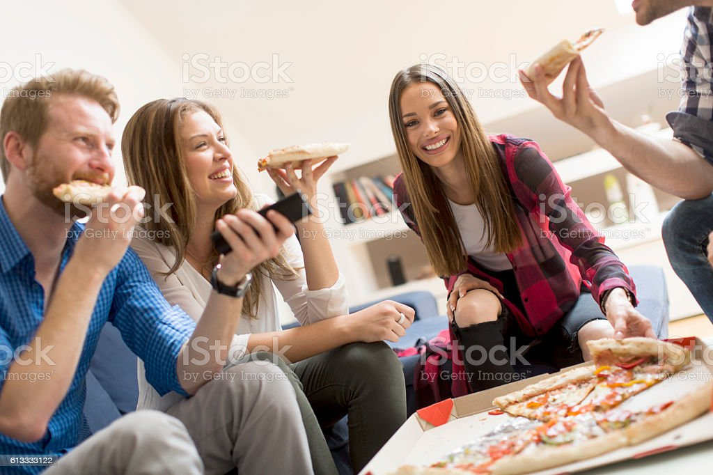 Friends eating pizza in th room stock photo