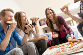 Friends eating pizza in th room