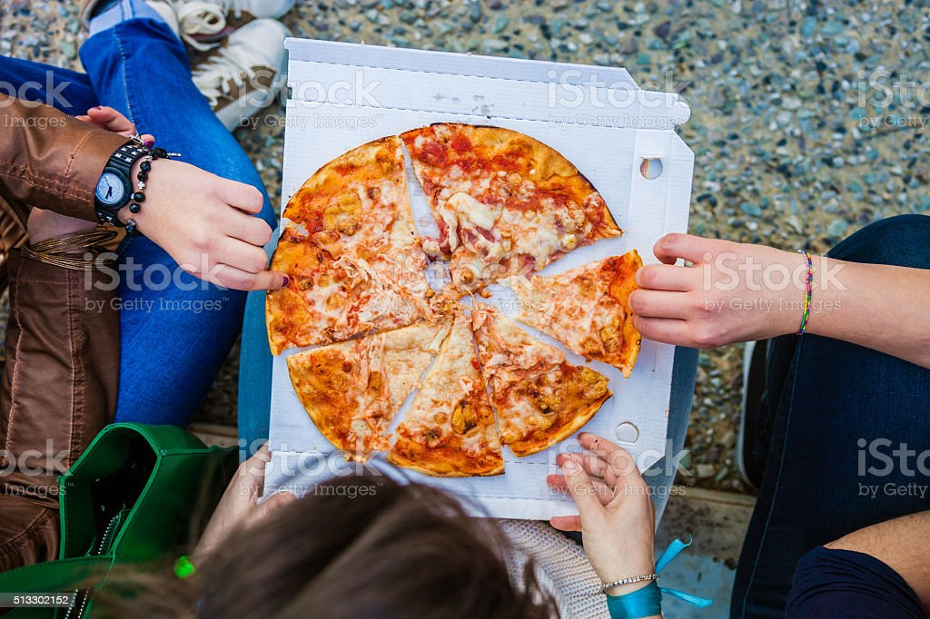 Friends eating Pizza on the streets stock photo