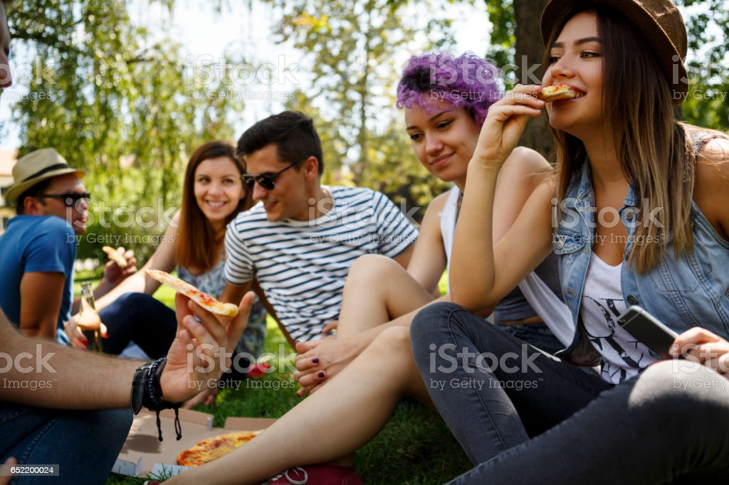 Friends eating pizza outside stock photo