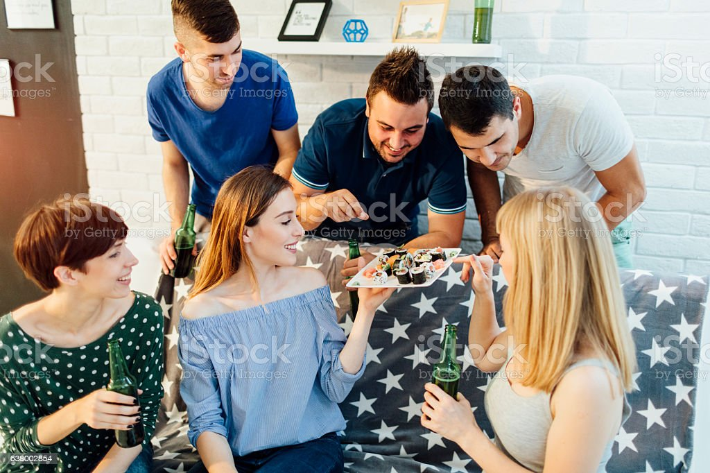 Friends Eating Sushi At Home Party. stock photo