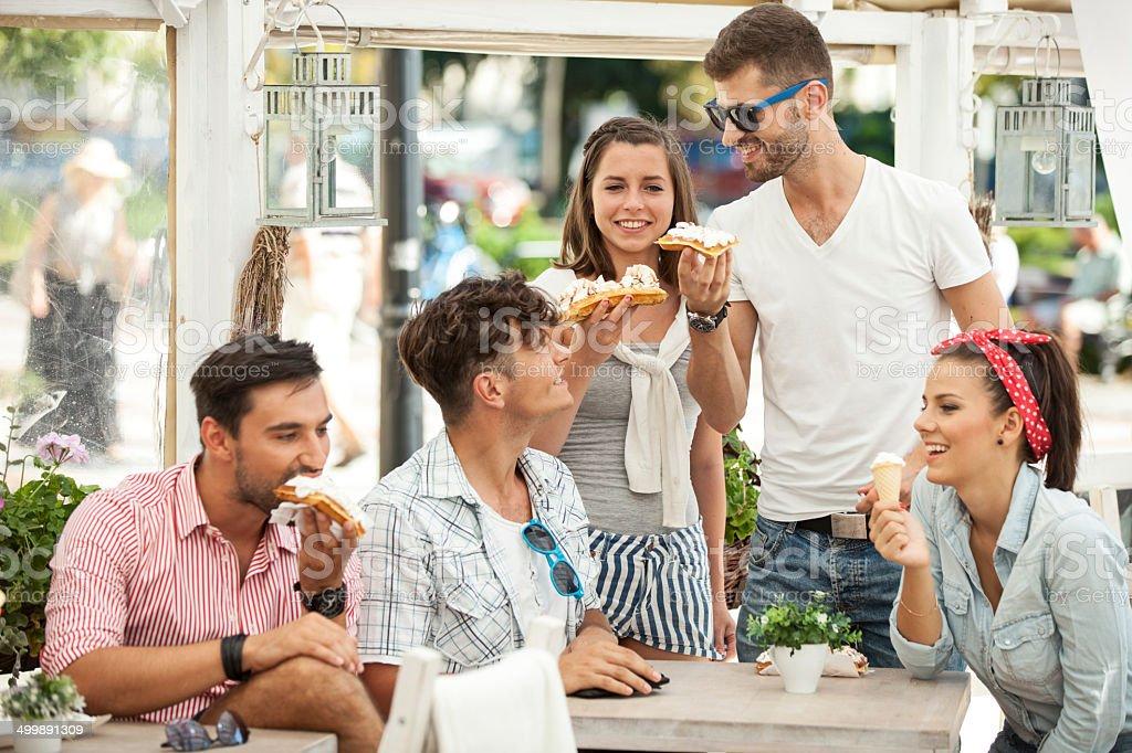 Friends Eating Waffles In Sidewalk Cafe stock photo