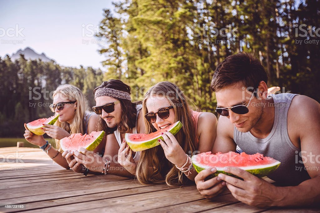 Friends eating watermelon by the lake stock photo