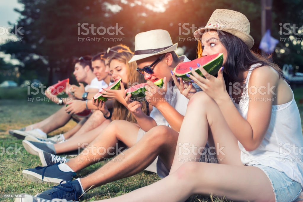 Friends eating watermelon in nature stock photo