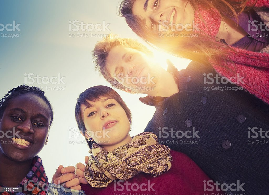 Friends embraced enjoy looking down at sunlight royalty-free stock photo