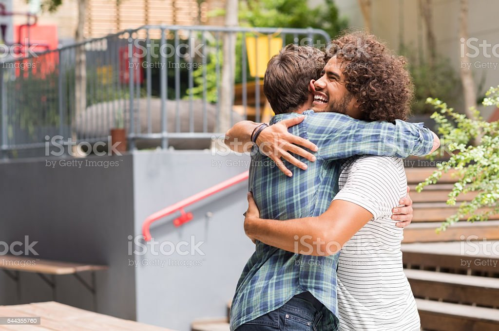 Friends embracing each other stock photo