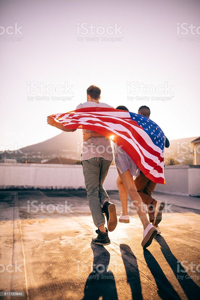Friends embracing wrapped with an American flag on rooftop stock photo
