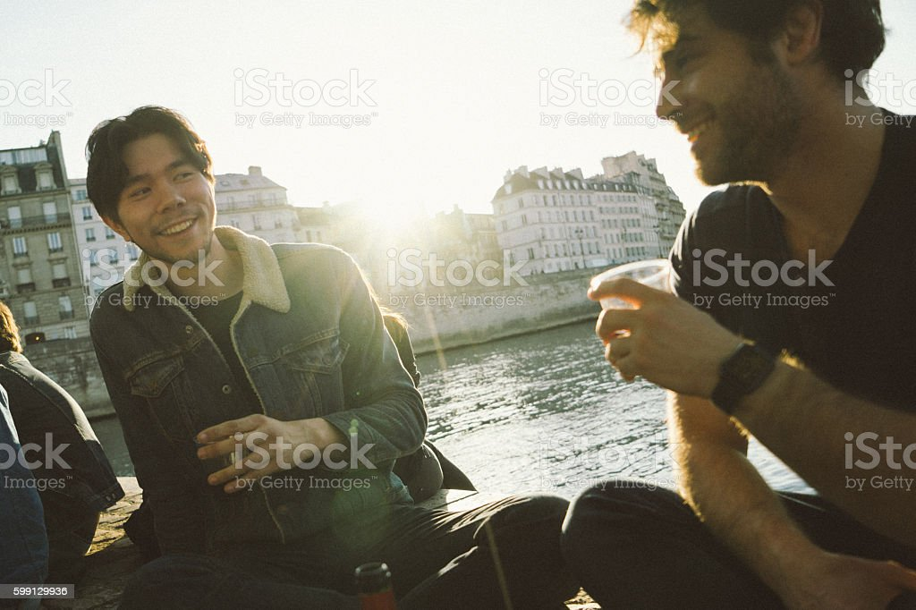 Friends enjoing sunset by the river and having wine stock photo