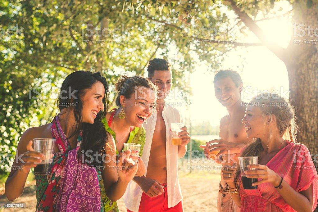 Friends enjoy sunset on the beach stock photo