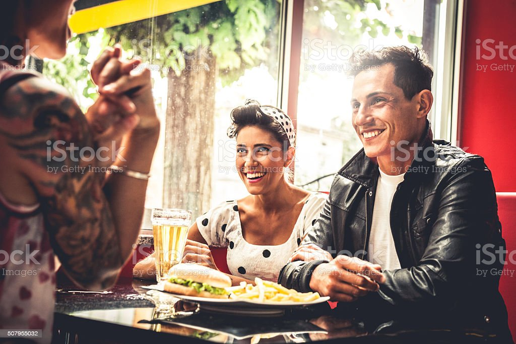 Friends enjoy together dinner in a cafe stock photo