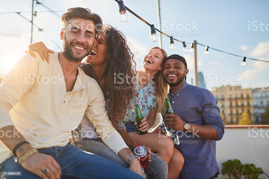 Friends enjoying a roof party in a bright suny day stock photo