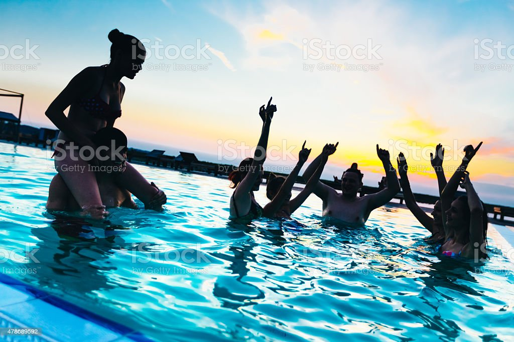Friends enjoying a sunset pool party stock photo