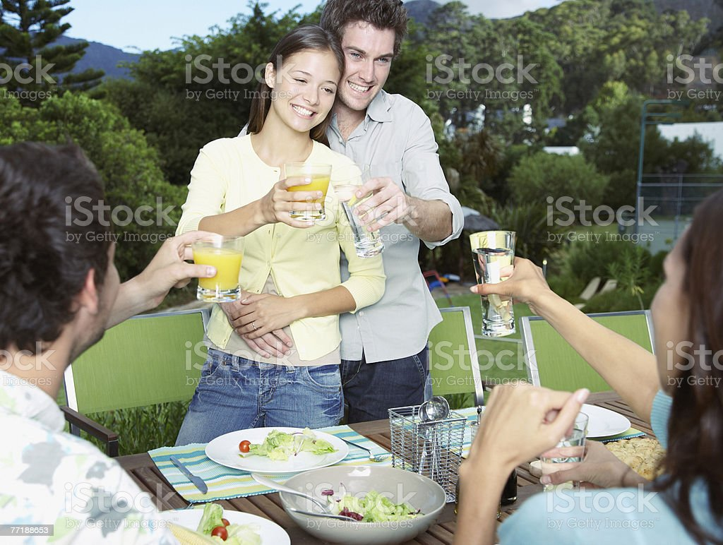 Friends enjoying an outdoor meal saluting their drinks royalty-free stock photo