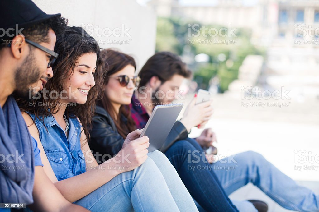 Friends enjoying and sharing a digital tablet. stock photo