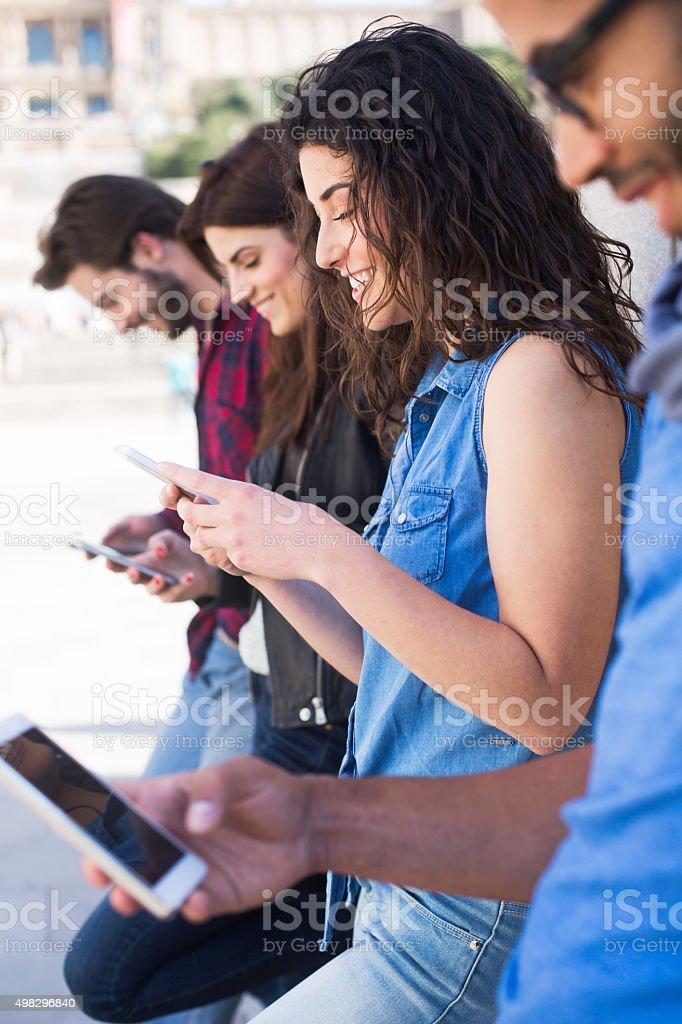 Friends enjoying and sharing technology stock photo
