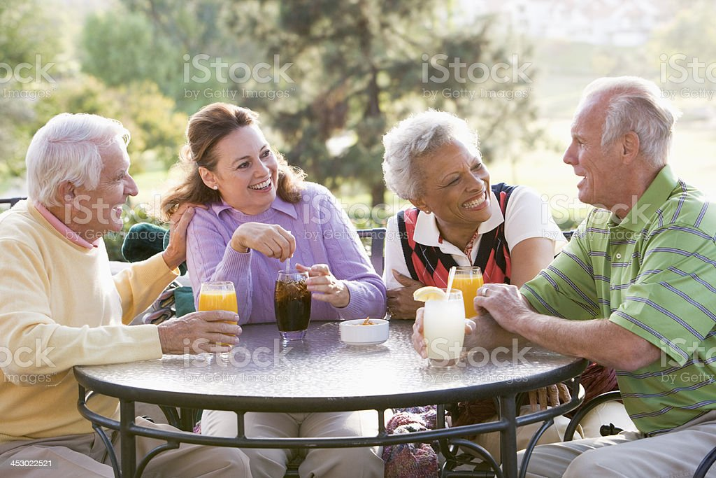 Friends Enjoying  Beverage By A Golf Course stock photo