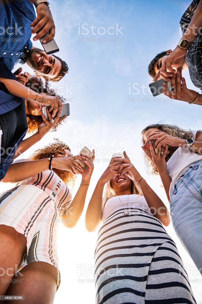 Friends enjoying city life using mobile phone stock photo