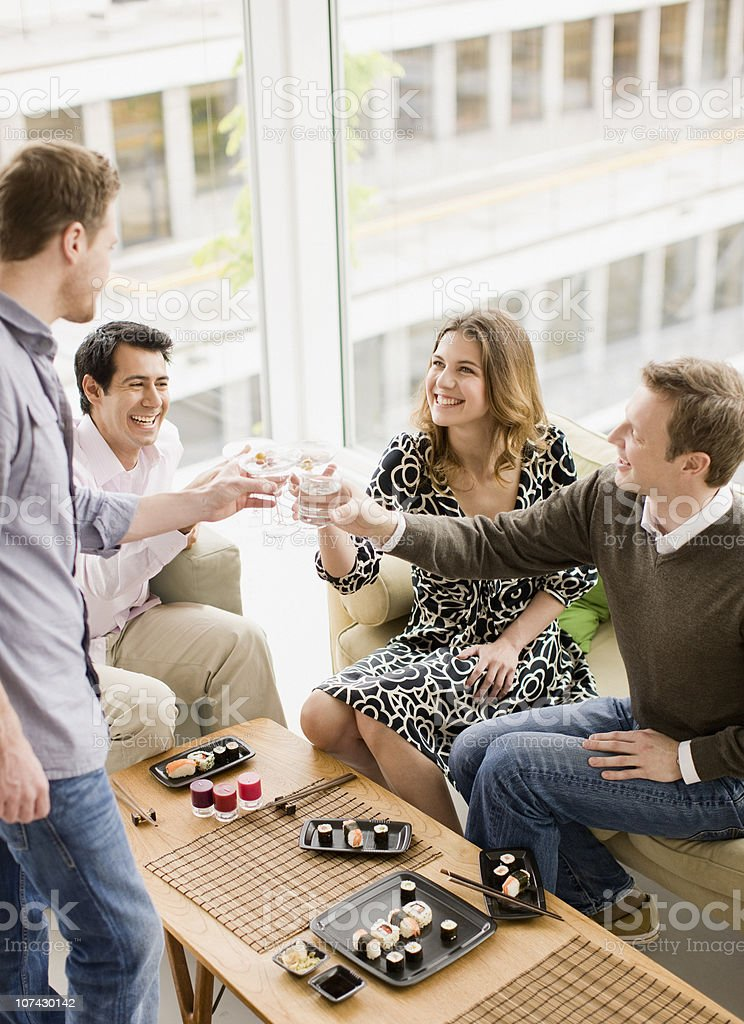 Friends enjoying cocktails and sushi at party royalty-free stock photo