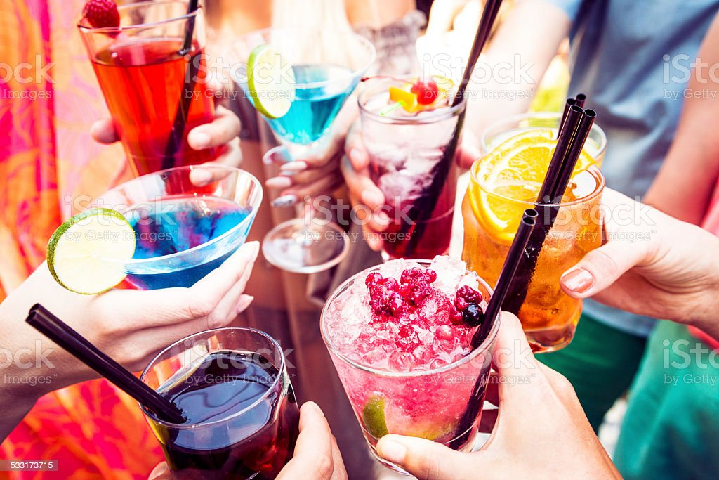friends enjoying cocktails at a party stock photo
