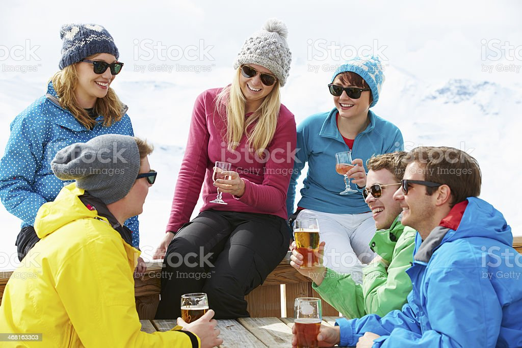 Friends enjoying drinks at a ski resort stock photo