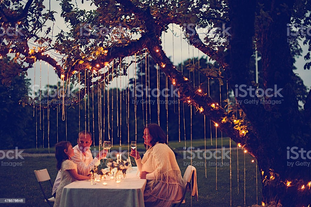 Friends enjoying evening summer party at night stock photo