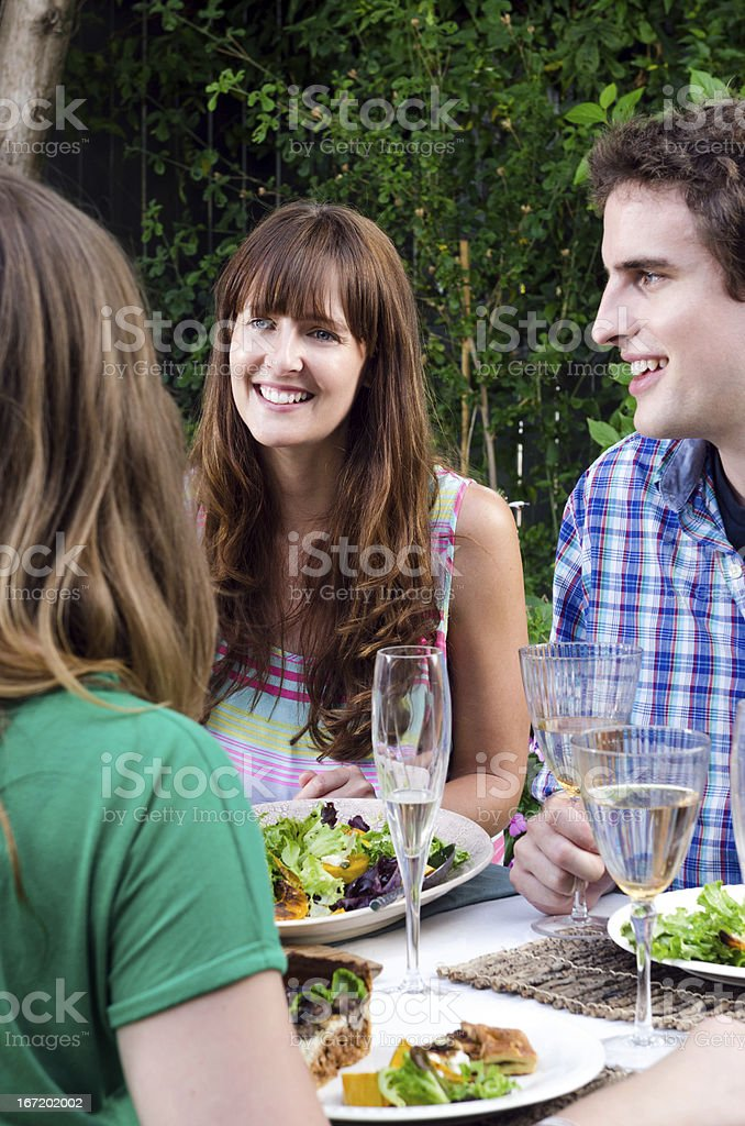 Friends enjoying food and drinks at a gathering royalty-free stock photo